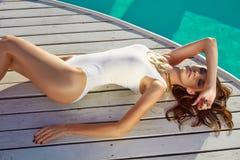 良好状态完善的棕褐色的皮肤的美丽的女孩在游泳池附近 图库摄影