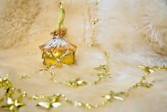 在绵羊毛皮背景的金黄圣诞节球与有金黄星的诗歌选 库存图片