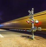 Железнодорожный переезд с проходить поезд к ноча Стоковые Изображения