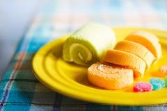 在黄色板材、软性和迷离概念的橙色和绿色草本卷蛋糕 免版税库存图片