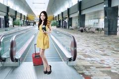 拿着护照和行李的华美的女孩 免版税库存照片