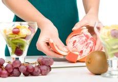 Ο μάγειρας ξεφλουδίζει το γκρέιπφρουτ για το επιδόρπιο φρούτων Στοκ Εικόνες