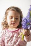 拿着花的一个美丽的小女孩的画象 免版税库存图片