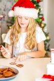 装饰圣诞节曲奇饼的女孩 免版税库存照片