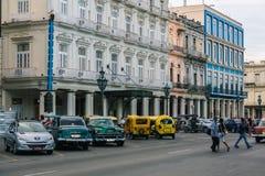 地道古巴人哈瓦那街道看法有经典减速火箭的葡萄酒汽车的在大厦和人民附近停放了背景横穿的 免版税库存图片