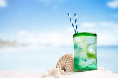 与冰、兰姆酒、柠檬和薄菏的鸡尾酒在海滩的一块玻璃 库存图片