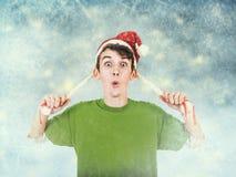 圣诞老人帽子的年轻人在蓝色结冰的背景 库存图片