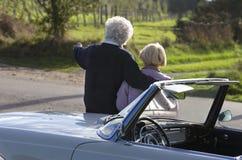 成熟夫妇后面看法乘汽车在乡下 免版税库存图片
