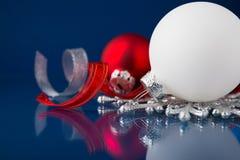 白色、银和红色圣诞节装饰品在深蓝背景 免版税库存图片