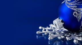 在深蓝背景的银色和蓝色圣诞节装饰品 免版税图库摄影