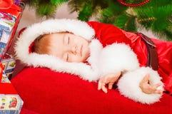 圣诞老人服装的婴孩睡觉在圣诞树的 免版税库存图片
