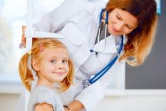 女孩的医生测量的高度 免版税库存照片