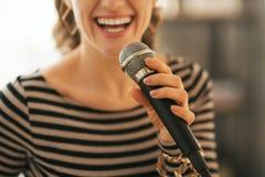 在唱歌与话筒的妇女的特写镜头 免版税库存照片