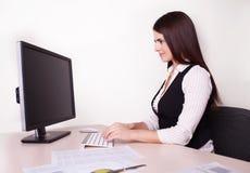 工作在她的书桌的快乐的女实业家看照相机  免版税图库摄影