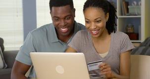 使用做的信用卡的微笑的年轻黑夫妇网上购买 免版税图库摄影
