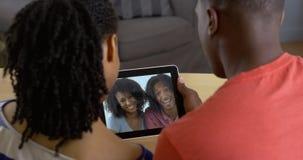 年轻黑夫妇谈话与在片剂计算机录影闲谈的朋友 库存照片