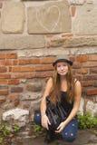 坐对在老镇的街道的墙壁的女孩 免版税库存图片