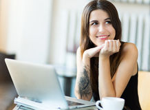 使用膝上型计算机的妇女在咖啡馆 图库摄影