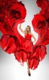 动态美丽的红色礼服的白肤金发的妇女 免版税库存照片