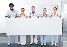 举行招贴的多种族医生 免版税库存图片