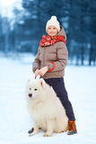 走与白色萨莫耶特人狗的愉快的少年男孩户外在公园在一个冬日 免版税图库摄影