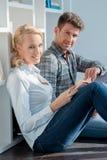 年轻夫妇坐地板在微型图书馆 免版税库存图片