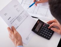 Человек проверяя фактуру на калькуляторе Стоковая Фотография RF