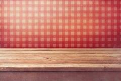 在被检查的红色墙纸的空的木甲板桌 葡萄酒厨房内部 库存照片