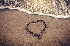 在沙子海海滩画的心脏被定调子的照片 免版税库存图片