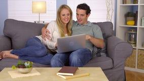 使用膝上型计算机的夫妇在长沙发 免版税库存图片