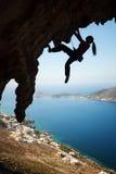 年轻女性攀岩运动员剪影峭壁的 免版税库存图片