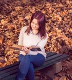 坐在平底船的长凳和读书的女孩 库存图片