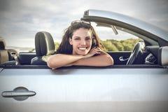 坐在汽车的微笑的女孩 免版税图库摄影
