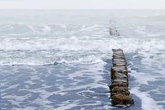 木防堤和波浪,风雨如磐的海天气 免版税库存照片