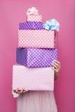 拿着有丝带的美丽的妇女的手一个五颜六色的大和小礼物盒 颜色箭深度域浅软件 圣诞节,生日,情人节 免版税库存照片