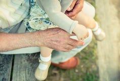 握老人手的手指女婴 免版税图库摄影
