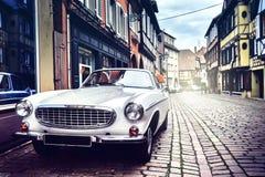 在老城市街道的减速火箭的汽车 免版税图库摄影