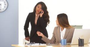 设法不同种族的女实业家结束在电话的一个成交 免版税库存图片