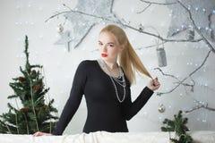 装饰圣诞树的俏丽的妇女 免版税库存图片