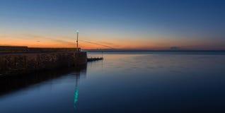 在日落的石防堤 库存照片