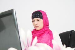 有膝上型计算机的美丽的年轻回教女商人在办公室 库存照片