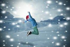 跳在雪的男孩 免版税库存图片