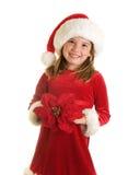 圣诞老人帽子和大一品红开花的一个逗人喜爱的小女孩 库存图片