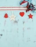 在水色蓝色木背景的现代红色和白色垂悬的圣诞节装饰 垂直 免版税库存照片