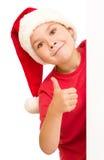 圣诞老人帽子的小女孩拿着空白的委员会 免版税库存照片