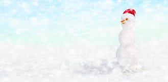 与圣诞老人帽子的雪人在他的在雪下的头 免版税库存图片