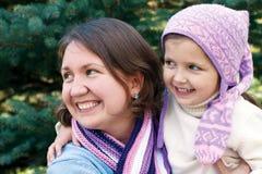拥抱在圣诞树附近的愉快的家庭 免版税库存照片