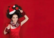 拿着在红色背景的愉快的圣诞节女孩一个棒棒糖 库存照片
