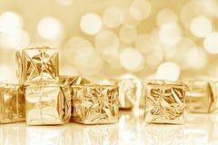 在发光的金黄纸的小圣诞节礼物 免版税库存图片