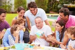 庆祝生日的多一代家庭在庭院里 免版税库存照片